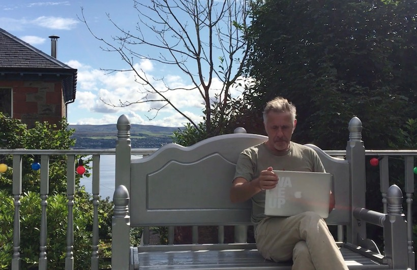 image of a man sitting on a bench in a garden overlooking the sea. He has a laptop on his knee demonstrating running an online business from home
