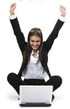 image of young woman sitting in front of her laptop. She is smiling and has her hands raised in celebration. She has found the best DIY WordPress themes for her online business