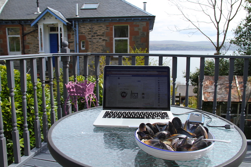 A laptop sits on an outside table on a deck overlooking the sea. Beside it are a plate of mussels, a glass of beer and a mobile phone. An example of the lifestyle possible when you embrace the digital world
