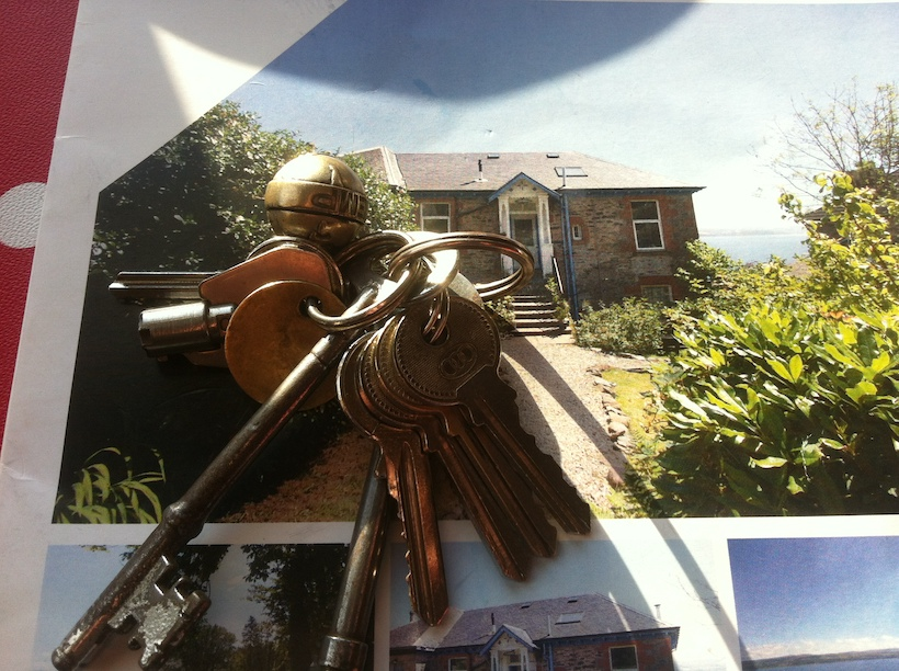 A sales brochure for a house overlooking the sea with a set of keys on top of it.