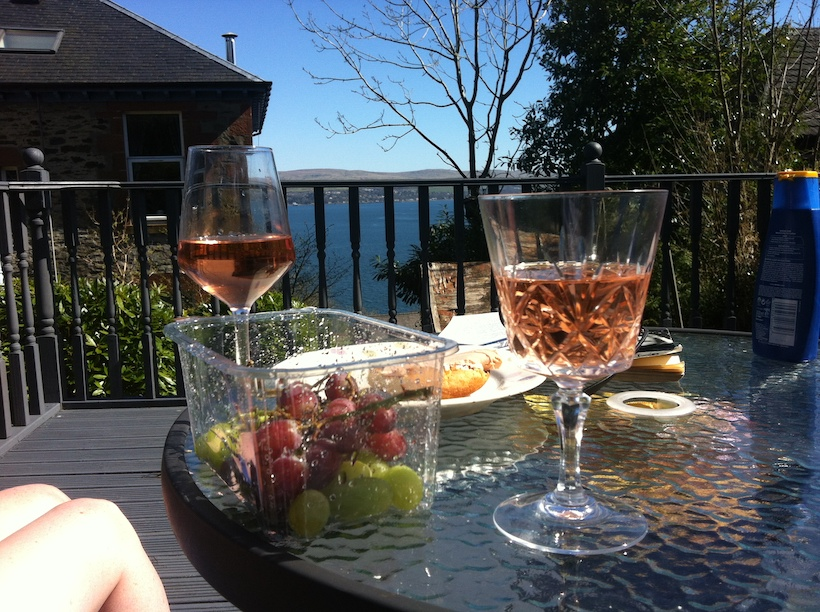 law of attraction. Photo of a table set on a sunlit deck overlooking the sea. It has two glasses of wine and some grapes on it