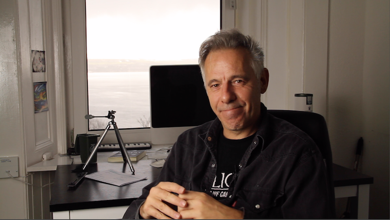 Image of a man in his 50's (Me) smiling from his home office which overlooks a seascape