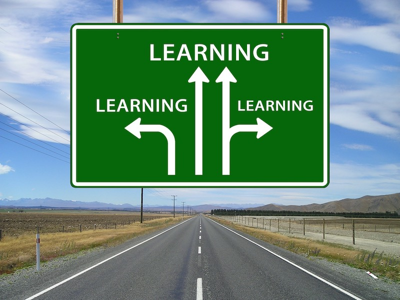 Image of an open road. A sign hangs above it with three arrows pointing up, left and right. All are headed Learning