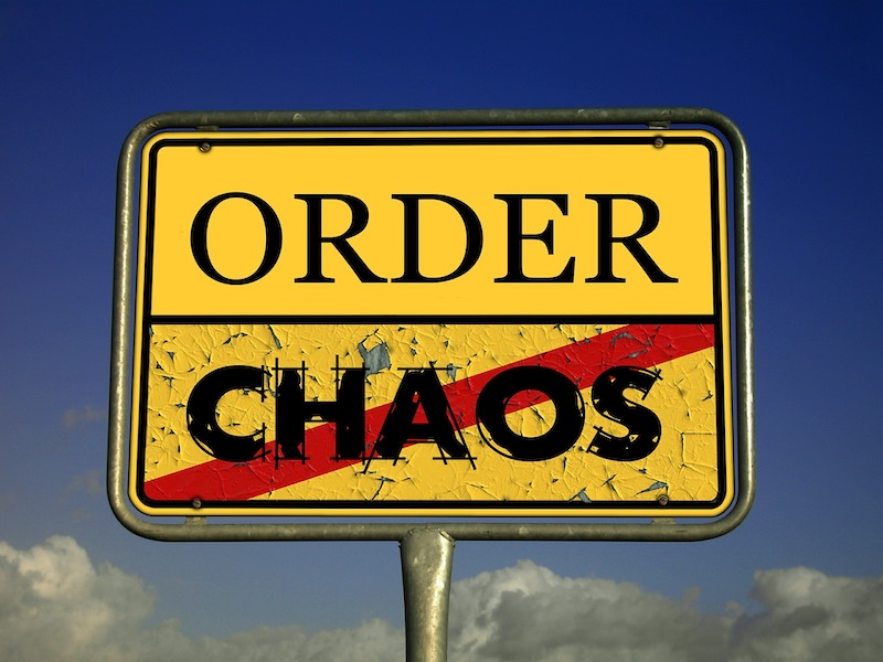 8 Ways Entrepreneurs Tackle Decision Paralysis - A signpost with order and chaos written on it. Chaos is tatty and the paint is cracking and it has a red line through it. Chaos is clear and immaculate looking