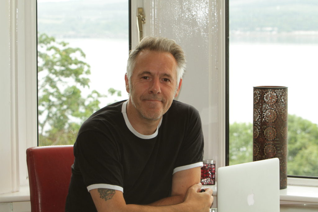 Picture of the author sitting at his home office overlooking the Firth of Clyde as an example of a more flexible lifestyle