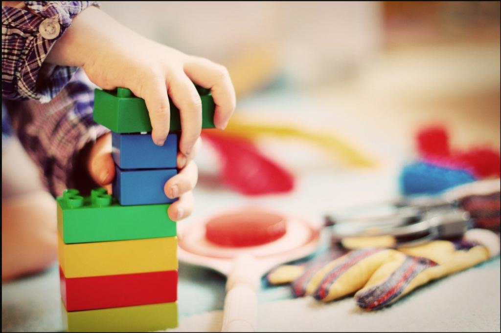 image of child building something with Lego bricks. Symbolises buiding something of your own in preparation for the coronavirus depression.